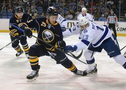 Buffalo Sabres center Mikhail Grigorenko (25), of Russia, is crossed-checked after a face-off from Tampa Bay Lightning center Cedric Paquette (13) during the first period of an NHL hockey game Wednesday, Dec. 31, 2014, in Buffalo, N.Y. The Buffalo Sabres have recalled three forwards, including Grigorenko, from the minors to fill their trade-depleted roster.THE CANADIAN PRESS/AP/Gary Wiepert
