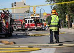 Emergency crews block traffic in both directions near Main and Higgins after power lines caught fire beneath the street.