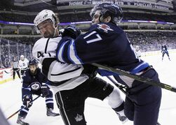 Winnipeg Jets forward Adam Lowry (17) checks Justin Williams of the Los Angeles Kings during second-period NHL action at the MTS Centre in Winnipeg Sunday. The Jets skated away with a 5-2 victory.