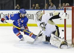 Pittsburgh Penguins goalie Marc-Andre Fleury (29) deflects a shot on goal by New York Rangers' Martin St. Louis (26) during the second period of Game 2 in the first round of the NHL hockey Stanley Cup playoffs Saturday, April 18, 2015, in New York. (AP Photo/Frank Franklin II)