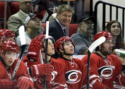 Carolina Hurricanes coach Bill Peters smiles during the first period of an NHL preseason hockey game against the Columbus Blue Jackets in Raleigh, N.C., Sunday, Sept. 21, 2014. (AP Photo/Gerry Broome)