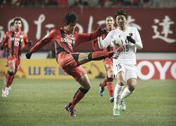 Lee Woong-hee, left, of South Korea's FC Seoul kicks the ball as Hiroyuki Takasaki of Japan's Kashima Antlers looks on during their Group H soccer match in the Asian Champions League at Seoul World Cup Stadium in Seoul, South Korea, Wednesday, March 4, 2015. FC Seoul defeated Kashima Antlers with 1-0. (AP Photo/Ahn Young-joon)