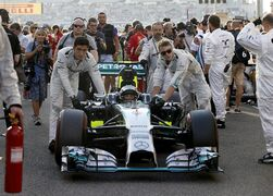 The car of Mercedes driver Nico Rosberg of Germany is pushed onto the starting grid before the Emirates Formula One Grand Prix at the Yas Marina racetrack in Abu Dhabi, United Arab Emirates, Sunday, Nov. 23, 2014. (AP Photo/Luca Bruno)