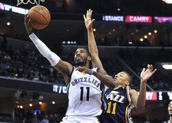 Memphis Grizzlies guard Mike Conley, left, shoots past Utah Jazz guard Dante Exum during the first half of an NBA basketball game Tuesday, March 3, 2015, in Memphis, Tenn. (AP Photo/Brandon Dill)