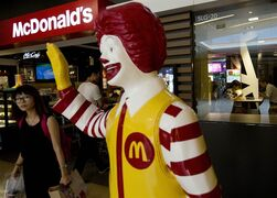 A Chinese customer walks past a statue of Ronald McDonald on display outside a McDonald's restaurant in Beijing, China Thursday, July 31, 2014. Global fast food chains are rushing to expand in China but even experienced operators face costly pitfalls in a fast-changing food supply industry plagued by repeated safety scandals. (AP Photo/Andy Wong)
