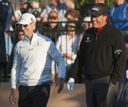 Phil Mickelson, right, and Zach Johnson walk off the 10th tee during the second round of the Valero Texas Open golf tournament, Friday, March 27, 2015, in San Antonio. (AP Photo/Darren Abate)