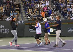 Serena Williams walks onto the court to speak to the fans after withdrawing from her match against Simona Halep, of Romania, at the BNP Paribas Open tennis tournament, Friday, March 20, 2015 in Indian Wells, Calif. (AP Photo/Mark J. Terrill)
