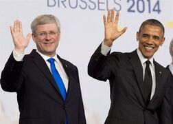 Canadian Prime Minister Stephen Harper and U.S. President Barack Obama wave during the G7 family photo Thursday June 5, 2014 in Brussels, Belgium. Plenty of diplomatic deals get done on the margins of global get-togethers, but one conducted on Twitter in 2014 made Prime Minister Stephen Harper a digital star among his fellow world leaders. THE CANADIAN PRESS/Adrian Wyld