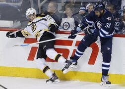 Winnipeg Jets' Dustin Byfuglien (33) checks Boston Bruins' Daniel Paille (20) during first period NHL action in Winnipeg on Friday.
