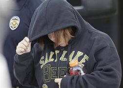 In this photo taken on Tuesday, Aug. 26, 2014, Alicia Marie Englert shields her face as she is escorted by police from a home in Kearns, Utah. Charging documents show Englert, a accused of dumping her newborn in a neighbour's trash, that she was afraid to tell her parents about the pregnancy. She was arrested Tuesday night on suspicion of attempted murder. The baby girl was in critical condition. (AP Photo/Rick Bowmer)