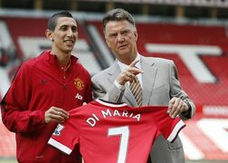Manchester United's new player Angel Di Maria left, and manager Louis van Gaal, pose for photographers holding his new shirt, at Old Trafford Stadium in Manchester, England, Thursday, Aug. 28, 2014. Manchester United have signed winger Angel Di Maria from Real Madrid for a British record transfer fee of �59.7m. The Argentine winger had a medical in Manchester on Tuesday and has signed a five-year deal. (AP Photo/Alastair Grant)