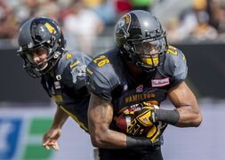 Hamilton Tiger-Cats running back Mossis Madu, right, takes a hand off from quarterback Zach Collaros against the Toronto Argonauts in Hamilton, Ont., Monday, Sept. 1, 2014. Madu is returning to the lineup just in time for the Tiger-Cats. The first-year running back missed Hamilton's 25-23 win last weekend against Edmonton with a hip pointer that also affected his back and spine. THE CANADIAN PRESS/Aaron Lynett