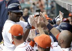 Houston Astros' Chris Carter, left, is congratulated by teammates after hitting a two-run home run against the Seattle Mariners during the first inning of a baseball game Saturday, Sept. 20, 2014, in Houston. Robbie Grossman scored on Carter's homer. (AP Photo/David J. Phillip)