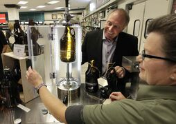 Ron Lemieux, minister responsible for Manitoba Liquor and Lotteries, watches Tracy Jones, a Liquor Mart customer service rep, place a Growler bottle in the filling equipment at the Kenaston Crossing Liquor Mart Friday