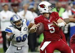 Arizona Cardinals quarterback Drew Stanton looks to pass under pressure from Detroit Lions defensive tackle Ndamukong Suh (90) during the first half of an NFL football game, Sunday, Nov. 16, 2014, in Glendale, Ariz. (AP Photo/Ross D. Franklin)