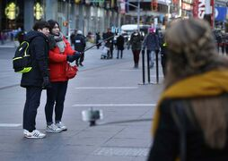 Tourists use selfie sticks to take their pictures in Times Square in New York in a file photo. Relatively new gadgets called selfie sticks make it easy to take your own wide-angled self-portraits or group shots. Fans say the expandable rods, which allow users to hold their cellphones a few feet away, are the ultimate convenience: no more bothering passers-by to take pictures, no more fretting about strangers taking lousy shots or running off with a pricey iPhone.