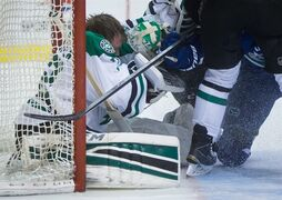 Vancouver Canucks' Derek Dorsett, right, pulls the mask off the face of Dallas Stars' goalie Kari Lehtonen, of Finland, during the first period of an NHL hockey game in Vancouver, British Columbia, on Wednesday, Dec. 17, 2014. (AP Photo/The Canadian Press, Darryl Dyck)