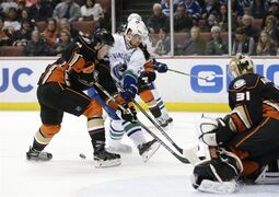 Anaheim Ducks' Cam Fowler, left, defends Vancouver Canucks' Daniel Sedin, of Sweden, during the first period of an NHL hockey game Sunday, Dec. 28, 2014, in Anaheim, Calif. (AP Photo/Jae C. Hong)