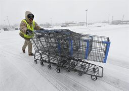FILE - In this March 12, 2014 file photo, Anthony Avery pushes grocery carts during a snow storm in Roseville, Mich. U.S. economic growth this year will likely be at the weakest pace since the Great Recession ended, the International Monetary Fund said Wednesday, July 23, 2014, mostly because of a sharp, weather-related contraction in the first quarter. (AP Photo/Paul Sancya, File)
