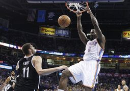 Oklahoma City Thunder's Kendrick Perkins (5) dunks in front of Brooklyn Nets' Brook Lopez (11) during the first quarter of an NBA basketball game in Oklahoma City, Friday, Nov. 21, 2014. (AP Photo/Sue Ogrocki)