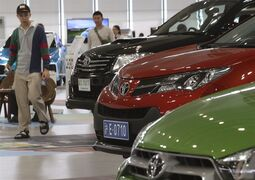 FILE - In this May 8, 2014 photo, visitors look at cars displayed at a Toyota gallery in Tokyo. Toyota Motor Corp. stayed at the top in global vehicle sales in 2014, but is pessimistic about this year. The Japanese automaker sold 10.23 million vehicles, beating out Volkswagen and General Motors to take that auto industry crown for the third year straight. Toyota was less upbeat about the future, expecting to sell fewer trucks and cars this year, at 10.15 million vehicles, down 1 percent year-on-year, according to numbers released Wednesday, Jan. 21, 2015. (AP Photo/Koji Sasahara, File)