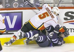 Calgary's Mark Giordano drills Winnipeg's Andrew Ladd in the first period.