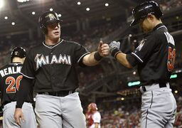 Miami Marlins' Justin Bour, left, celebrates his home run with Ichiro Suzuki, right, of Japan, during the seventh inning of a baseball game, Monday, May 4, 2015, in Washington. The Nationals won 6-4. (AP Photo/Nick Wass)