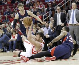 Houston Rockets' Donatas Motiejunas, center, passes off the ball from the floor between Atlanta Hawks Kyle Korver, left, and Mike Scott (32) in the first half of an NBA basketball game Saturday, Dec. 20, 2014, in Houston. (AP Photo/Pat Sullivan)