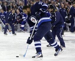 The Jets' Dustin Byfuglien of Team Foligno, takes a slapshot during the Hardest Shot competition during the NHL All-Star hockey skills competition in Columbus, Ohio.