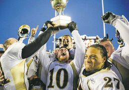 University of Manitoba quarterback Jordan Yantz (centre) lifts the Hardy Cup after the Bisons' stunning upset of Calgary in the Canada West final.