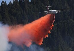 A jet aerial tanker drops its load of fire retardant on a fire near Pollack Pines, Calif., Monday, Sept. 15, 2014. THE CANADIAN PRESS/AP, Rich Pedroncelli