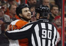 Philadelphia Flyers center Zac Rinaldo looks up as he is being held back by linesman Andy McElman during the third period of an NHL hockey game against the Vancouver Canucks in Philadelphia on Jan. 15, 2015. The NHL has suspended Flyers forward Zac Rinaldo for eight games for charging and boarding Penguins defenceman Kris Letang. THE CANADIAN PRESS/AP, Chris Szagola