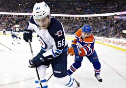 Winnipeg Jets forward Adam Lowry (56) and the Edmonton Oilers' Brad Hunt battle in the corner during first-period action in Edmonton Monday.