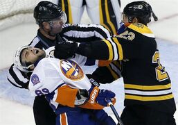 New York Islanders left wing Cory Conacher (89) falls back after being punched by Boston Bruins center Chris Kelly (23) despite the efforts of linesman Derek Nansen (70) during the third period of an NHL preseason hockey game in Boston, Tuesday, Sept. 30, 2014. The Islanders won 5-3. (AP Photo/Elise Amendola)