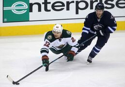 Minnesota Wild's Nino Niederreiter and Winnipeg Jets forward Matt Halischuk fight for the puck during the first period.
