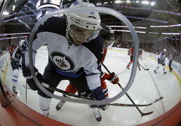 Winnipeg Jets' Evander Kane (9) battles with New Jersey Devils' Damon Severson (28) during first period NHL hockey action at the Prudential Center in Newark, N.J., Thursday.