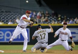 Arizona Diamondbacks' Nick Ahmed forces out Pittsburgh Pirates' Gaby Sanchez (17) as he turns a double play on Pirates' Russell Martin during the eighth inning of a baseball game, Thursday, July 31, 2014, in Phoenix. At right is Diamondbacks' Aaron Hill. (AP Photo/Matt York)