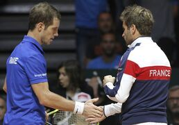 France's Richard Gasquet, left, and team captain Arnaud Clement tap their hands as he plays Switzerland's Roger Federer during the Davis Cup final match in Lille, northern France, Sunday, Nov.23, 2014. (AP Photo/Christophe Ena)