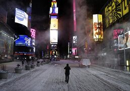 A pedestrian walks in the middle of Seventh Avenue in Times Square, New York, early Tuesday, Jan. 27, 2015. A storm packing blizzard conditions spun up the East Coast early Tuesday, pounding parts of coastal New Jersey northward through Maine with high winds and heavy snow. (AP Photo/Seth Wenig)