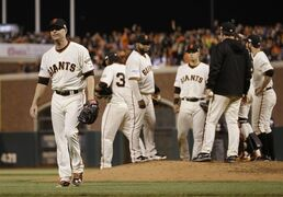 San Francisco Giants pitcher Tim Hudson, left, walks off the mound after being relieved during the sixth inning of Game 3 of baseball's World Series against the Kansas City Royals Friday, Oct. 24, 2014, in San Francisco. (AP Photo/Matt Slocum)