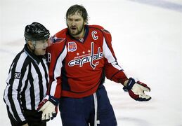 Linesman Andy McElman escorts Washington Capitals left wing Alex Ovechkin (8), from Russia, to the penalty box after a fight in the third period of an NHL hockey game against the Pittsburgh Penguins, Wednesday, Jan. 28, 2015, in Washington. The Capitals won 4-0. (AP Photo/Alex Brandon)