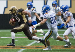 The Manitoba Bisons' Nic Demski (#9) evades the UBC Thunderbirds Saturday afternoon at Investors Group Field. The Bisons won 20-10.