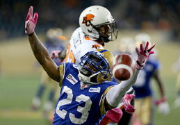 Winnipeg Blue Bombers' Desia Dunn (23) reaches for the ball as he covers BC Lions' Lavasier Tuinei (82) on Saturday.