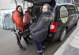 RMTC's Kathryn Ball (from left), Heather Russell, and Aryn Lancaster load up a van outside the RMTC's Market Avenue theatre on Jan. 27  in preparation for the regional tour. They'll be away until the tour's final show in Virden on March 7.