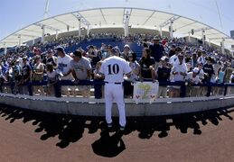 Milwaukee Brewers manager Ron Roenicke signs autographs before the Brewers' spring training baseball game against the Cleveland Indians in Phoenix on Saturday, March 28, 2015. (AP Photo/Chris Carlson)