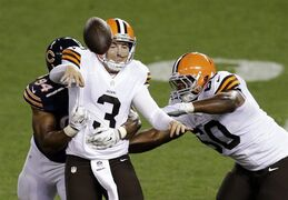 Cleveland Browns quarterback Rex Grossman (3) throws an incomplete pass after being hit by Chicago Bears defensive end Cornelius Washington (94) in the third quarter of a preseason NFL football game Thursday, Aug. 28, 2014, in Cleveland. (AP Photo/Tony Dejak)