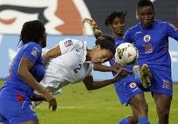 United States forward Sydney Leroux (2) dives in an attempt to head the ball as Haiti defenders Kencia Marseille, left, Yvrose Gervil, and Roselord Borgella (18) defend, during the second half of a CONCACAF soccer match, at RFK Stadium, Monday, Oct. 20, 2014, in Washington. USA won 6-0. (AP Photo/Alex Brandon)