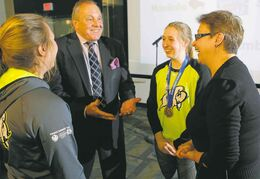 Ministers Melanie Wight (right) and Ron Lemieux (second from left) chat with  ringette gold medallists Raeanne Wysocki (left) and Ryann Bannerman.
