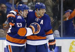 New York Islanders' Kyle Okposo, right, celebrates with Casey Cizikas (53), who scored a goal against the Tampa Bay Lightning during third period NHL hockey action in Uniondale, N.Y., on Nov. 18, 2014. The surprising New York Islanders are starting the second half on a down note as top-line forward Kyle Okposo will be sidelined six to eight weeks because of an undisclosed upper-body injury. THE CANADIAN PRESS/AP, Kathy Willens