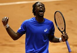 France's Gael Monfils celebrates a winning point as he plays Switzerland's Roger Federer during the Davis Cup final in Lille, northern France, Friday, Nov.21, 2014. (AP Photo/Peter Dejong)